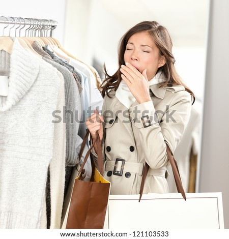 Tired woman yawning while shopping clothes in clothing store shop. Beautiful young mixed race Asian / Caucasian female model.