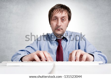 Tired worker typing on the keyboard. Selective focus on the man head. - stock photo
