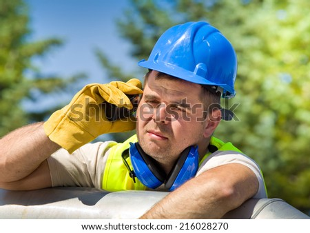 Tired worker with walkie talkie and safety equipment on oil plant  - stock photo
