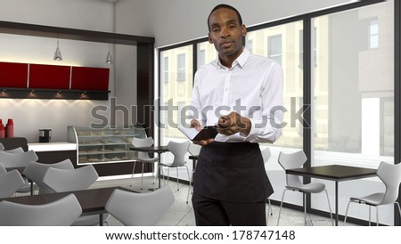 tired young African-American waiter in a coffeeshop