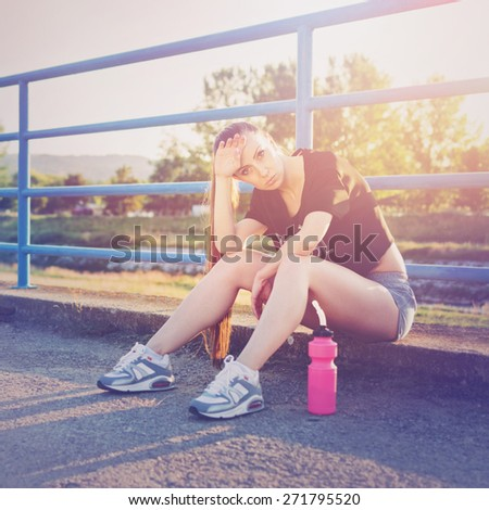Tired young brunette Caucasian woman sitting relaxing after running. Beautiful fitness girl taking a break after jogging outdoors on sunny summer day. Square format, retouched, filter applied. - stock photo