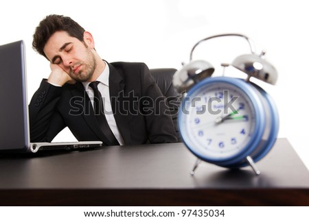 Tired young business man sleeping next to his laptop computer at the desk, isolated on white - stock photo