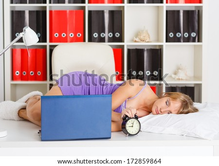 Tired young business woman is sleeping on workplace in the office. - stock photo