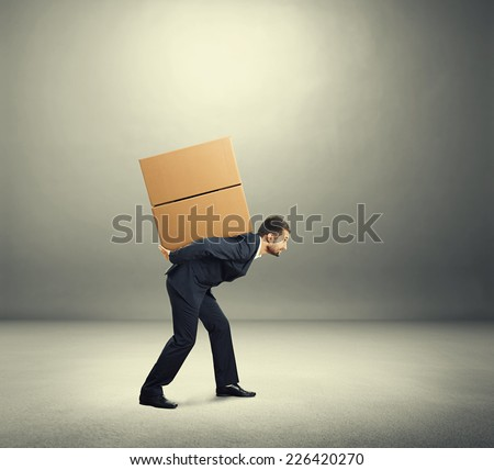 tired young businessman carrying on the back two heavy boxes. photo in the grey room