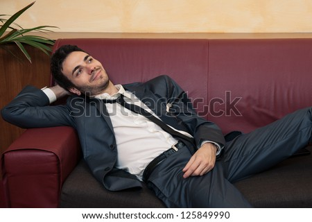 Tired young businessman relaxing on sofa.