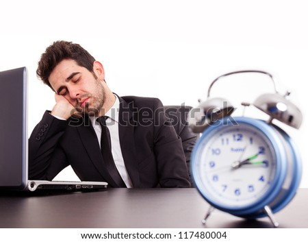 Tired young businessman sleeping next laptop on white background - stock photo