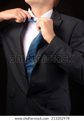 Tired young businessman taking off his tie. Isolated on black - stock photo