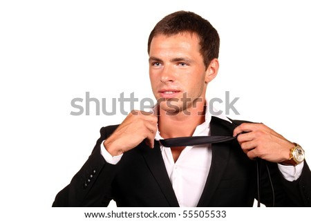 Tired young businessman taking off his tie. Isolated on white.