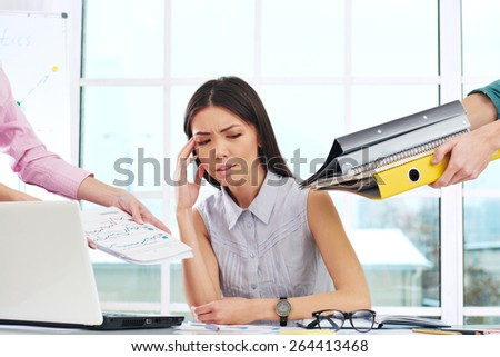 Tired young businesswoman looking at hands with folders around her. Office interior with window. Concept for overworking - stock photo