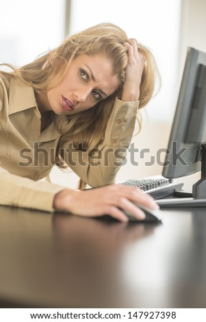 Tired young businesswoman looking away while sitting at computer desk in office - stock photo