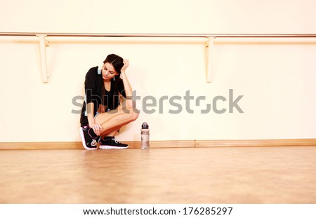 Tired young fit woman leaning on the wall at gym