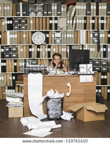 Tired Young Girl at a messy office - stock photo