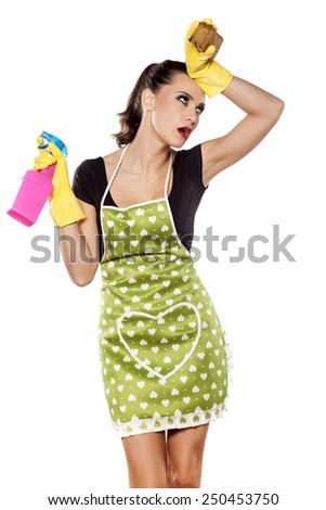 Tired young housewife posing on a white background - stock photo