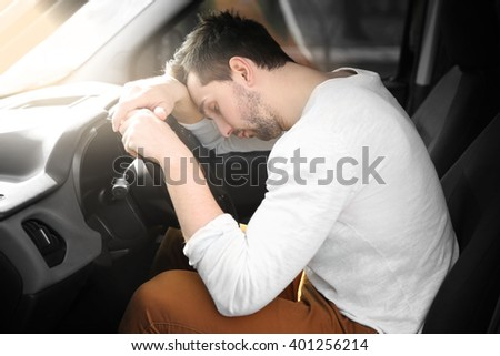 Tired young man asleep on steering wheel in his car. - stock photo