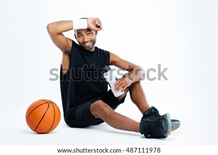 Tired young man basketball player sitting and drinking water over white background