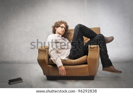 Tired young man lying on an armchair - stock photo