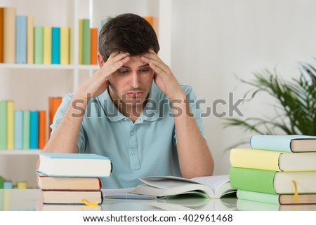 Tired Young Man Reading Book In Library