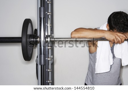 Tired young man resting on barbell after workout at gym - stock photo