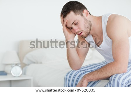 Tired young man sitting on his bed looking away from the camera