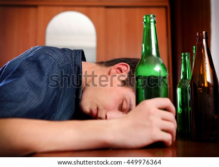 Tired Young Man with Bottle of the Beer at the Home - stock photo