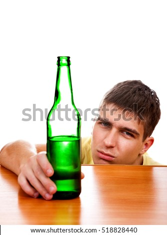 Tired Young Man with the Beer at the Table on the White Background