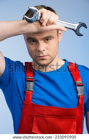 Tired young mechanic in red overall on blue background. closeup of man holding wrench and wiping sweat of fore head - stock photo