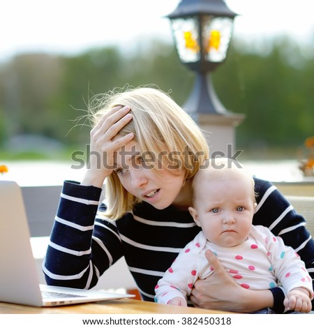 Tired young mother working oh her laptop and holding 6-month daughter - stock photo