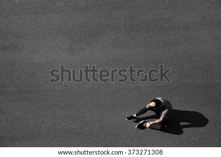 Tired young runner leaning over to catch his breath. Jogger asphalt after running and training exercise outside in summer. Caucasian man sports model. - stock photo