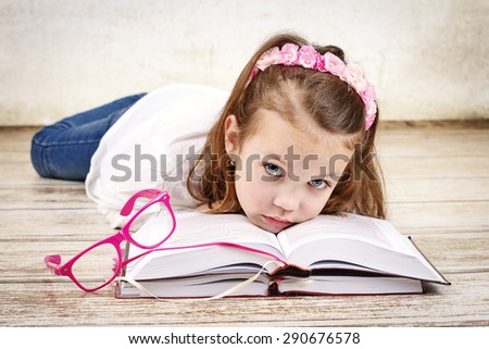 Tired young schoolgirl with books - stock photo