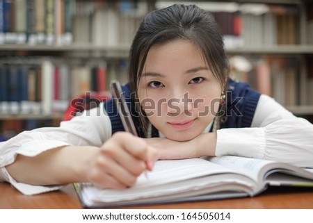 Tired young student resting her head on a textbook and doing homework in front of a library bookshelf