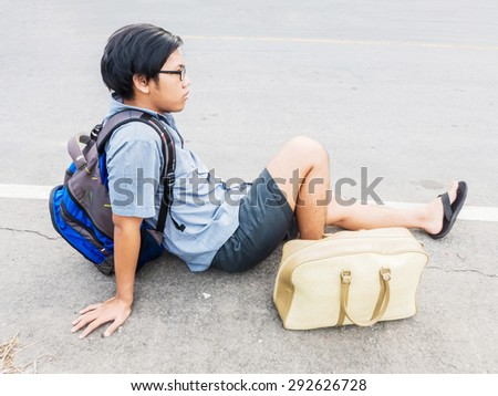 Tired young traveling man sit on the road