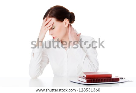 Tired young woman at a table with books, white background - stock photo