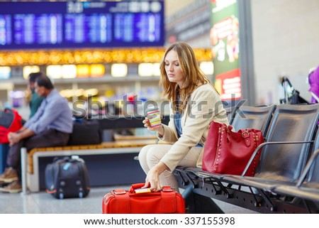 Tired young woman at international airport sitting and drinking coffee in terminal. Upset passenger waiting. Canceled flight due to pilot strike. - stock photo