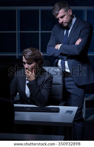 Tired young woman at work in night and her boss