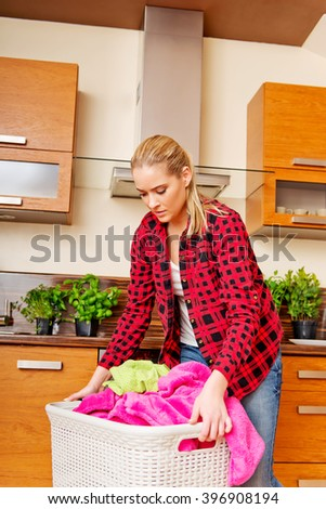 Tired young woman carrying laundry basket in kitchen - stock photo