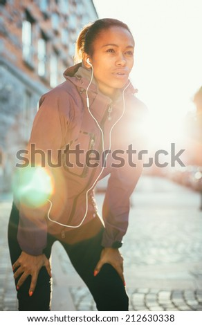 Tired young woman catching breath after a long run in city - stock photo
