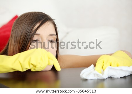 Tired young woman cleaning furniture table in yellow gloves - stock photo