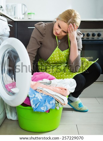 Tired young woman doing laundry with washing machine at home kitchen - stock photo