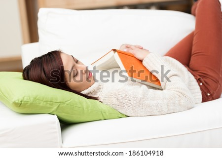 Tired young woman fallen asleep while reading lying on her back on a comfortable couch with her book lying on her chest - stock photo