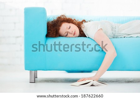 Tired young woman  lying on a sofa  at home with a book  - stock photo