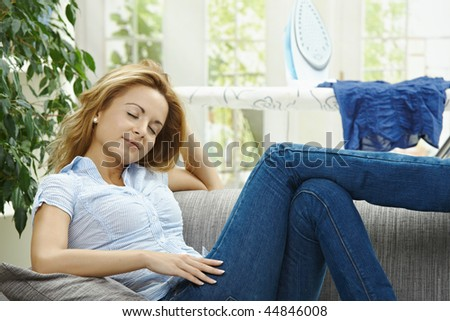 Tired young woman resting on couch, having a break during housework.