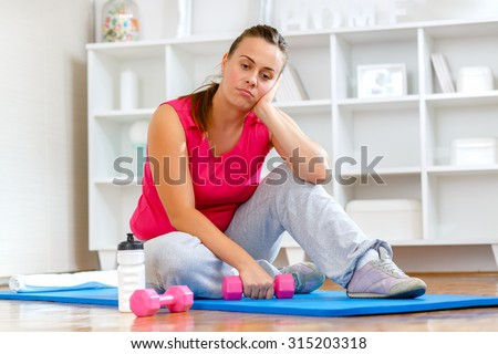 Tired young woman struggling to get back into shape.  - stock photo