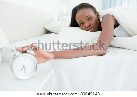 Tired young  woman switching off her alarm clock in her bedroom - stock photo