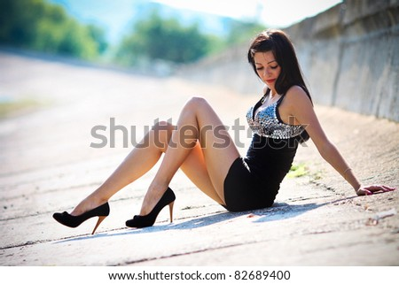 Tired young woman with closed eyes sitting down on road