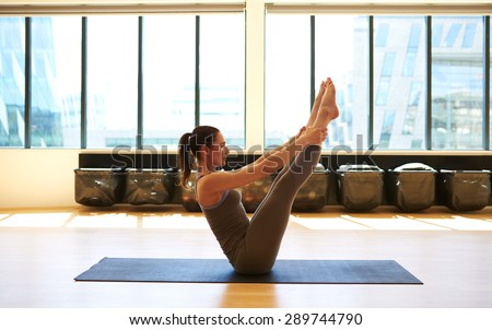Tireless woman is holding her legs with her arms to strengthen the abdominal muscles - stock photo