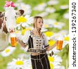 tiroler summer party with a sexy woman or girl in traditional austrian or german oktoberfest clothes holding a big glass of beer in her hands and on the background white and yellow farmland flowers - stock photo