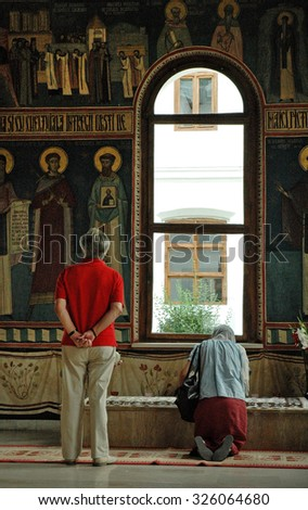 TISMANA, ROMANIA - AUGUST 21, 2008: People praying at the grave of Saint Nicodim, the reorganizer of Romanian monasticism in the Monastery of Tismana