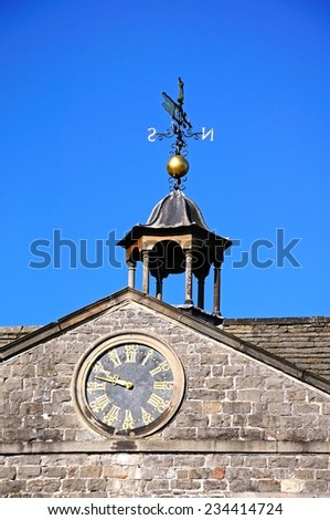TISSINGTON, UK - SEPTEMBER 7, 2014 - Clock and weathervane detail on top of Tissington Hall, Tissington, Derbyshire, England, UK, Western Europe, September 7, 2014.