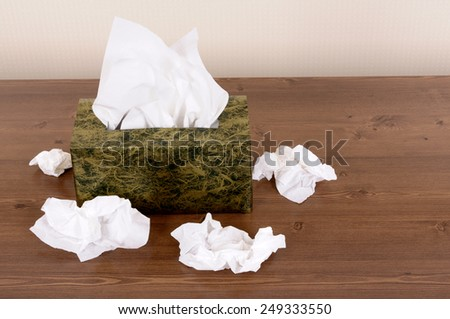 Tissue box, used tissues on wood table.  Copy space. - stock photo