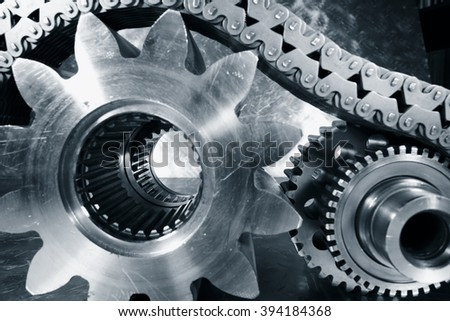 titanium and steel cogwheels and gears powered by chains - stock photo